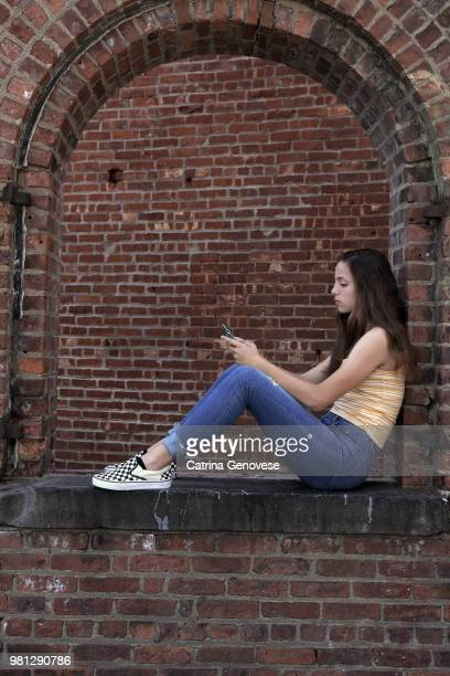Portrait of 16 year old teenage girl sitting in an open arch brick window with a brick wall background looking at mobile phone