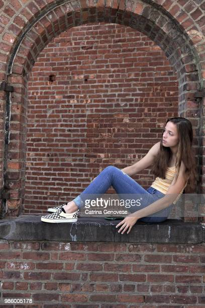 Portrait of 16 year old teenage girl sitting in an open arch brick window with a brick wall background looking at someone or something