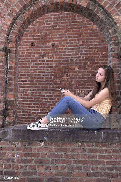 Portrait of 16 year old teenage girl sitting in an open arch brick window with a brick wall background looking at someone or something holding cell phone