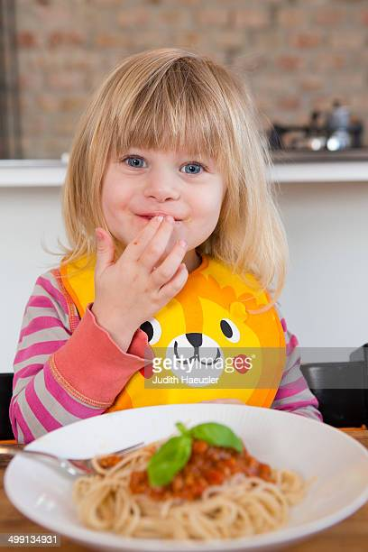 Portrait of 2 year old girl eating spaghetti with fingers