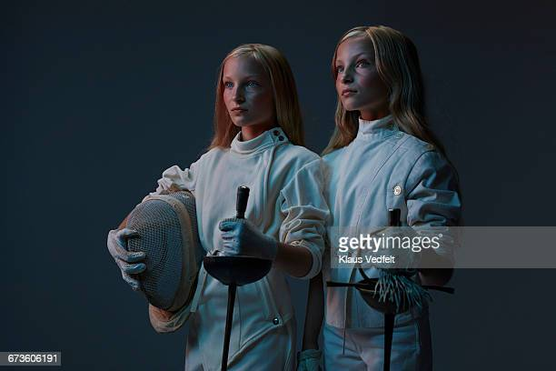 Portrait of 2 young twin fencers looking out