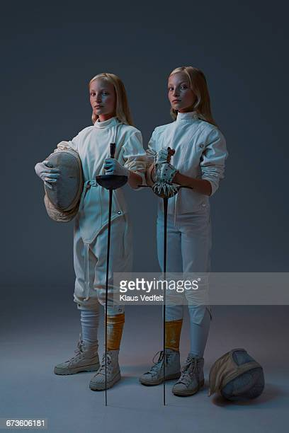 Portrait of 2 young twin fencers looking to camera