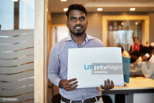 portrait of 27 year old indian businessman holding sign - printed sleeve stock pictures, royalty-free photos & images