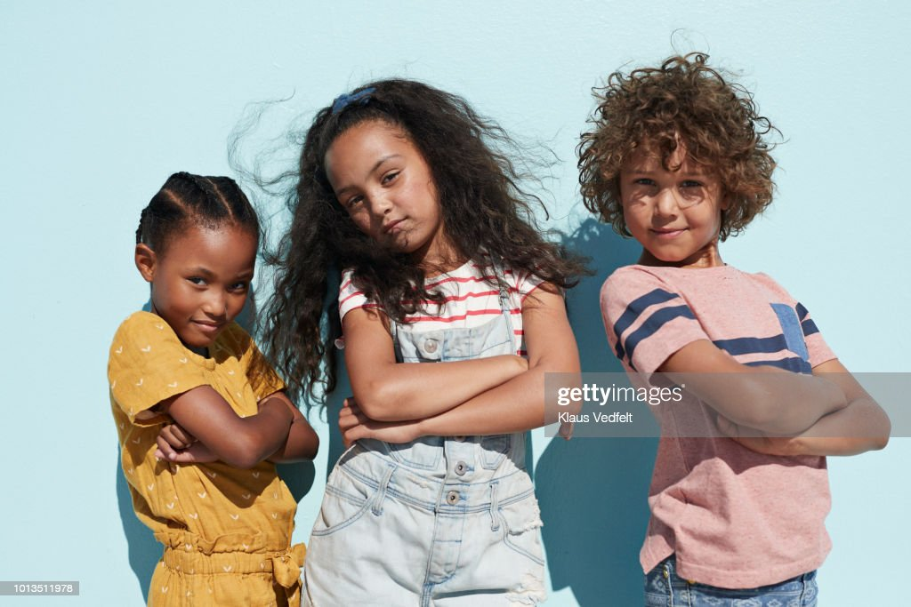 Portrait of 3 cool kids together on blue backdrop in summer : Stock Photo
