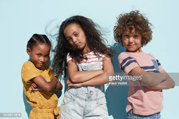 portrait of 3 cool kids together on blue backdrop in summer - children only stock pictures, royalty-free photos & images