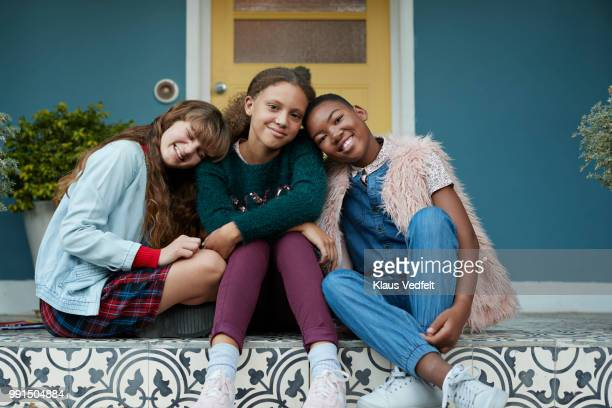 Portrait of 3 happy girlfriends, relaxing on porch