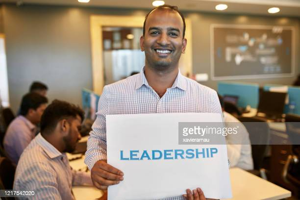 portrait of 32 year old indian businessman holding sign - printed sleeve stock pictures, royalty-free photos & images