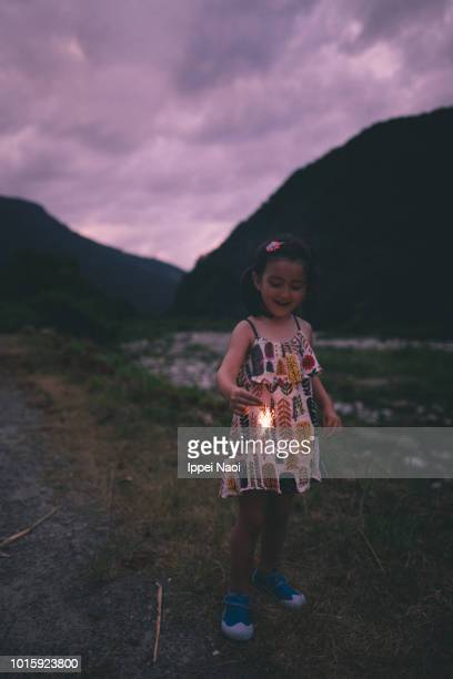 Portrait of 4 year old girl enjoying fireworks at twilight, Japan