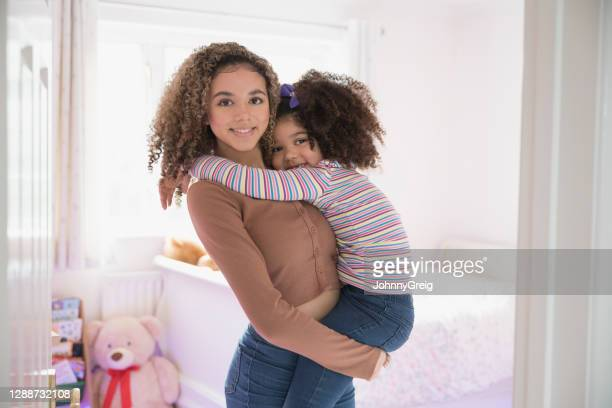 portrait of 5 and 17 year old mixed race sisters at home - mid length hair stock pictures, royalty-free photos & images