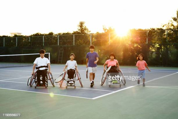 portrait of 5 young athletes, two teenage boys in a wheelchair, one teenage boy standing, one teenage girl in a wheelchair and one young girl standing on a tennis court - 車いすテニス ストックフォトと画像