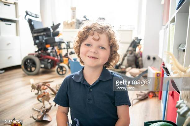 portrait of 6 year old boy sitting in playroom, wheelchair in background - day 7 foto e immagini stock