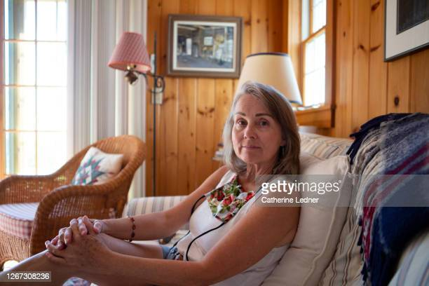 portrait of 60's woman on sofa in seaside cabin with protective face mask loose around her neck - catherine ledner stock pictures, royalty-free photos & images