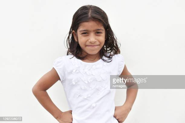 portrait of 6-7 years cute little girls standing against white wall - 6 7 years stock pictures, royalty-free photos & images
