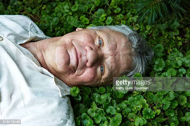 Portrait of 70 year old man reclining in grass