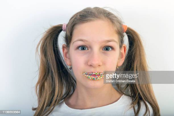 portrait of a 10 years old girl with sugar sprinkles on her lips - 10 11 anni foto e immagini stock