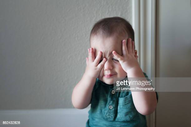 portrait of a 12 month old twin baby plays peek a boo while playing at home - naughty america - fotografias e filmes do acervo