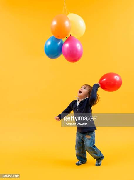 Portrait of a 2 year old boy over yellow background