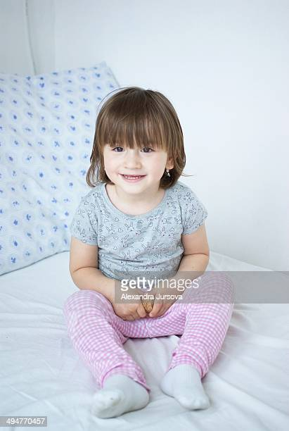 Portrait of a 2 years old girl sitting on the bed.
