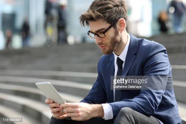 portrait of a 30 years old man in a business district - mid adult men stock pictures, royalty-free photos & images