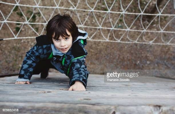Portrait of a 6 year old boy climbing