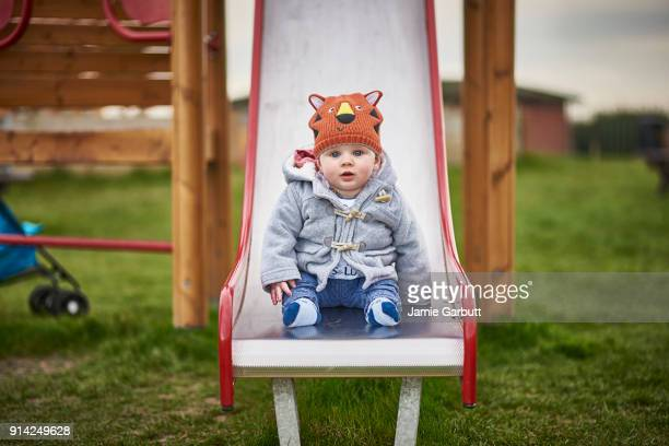 Portrait of a 8 month old British male sat on a slide