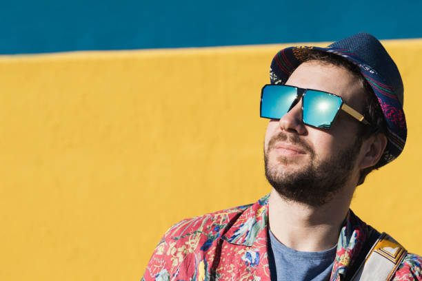 Portrait of a a handsome guy with beard, funny sunglasses, hat and tropical clothes on a blue and yellow background