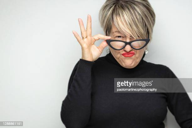 a portrait of a adult woman making a face against white background - confrontation stock pictures, royalty-free photos & images