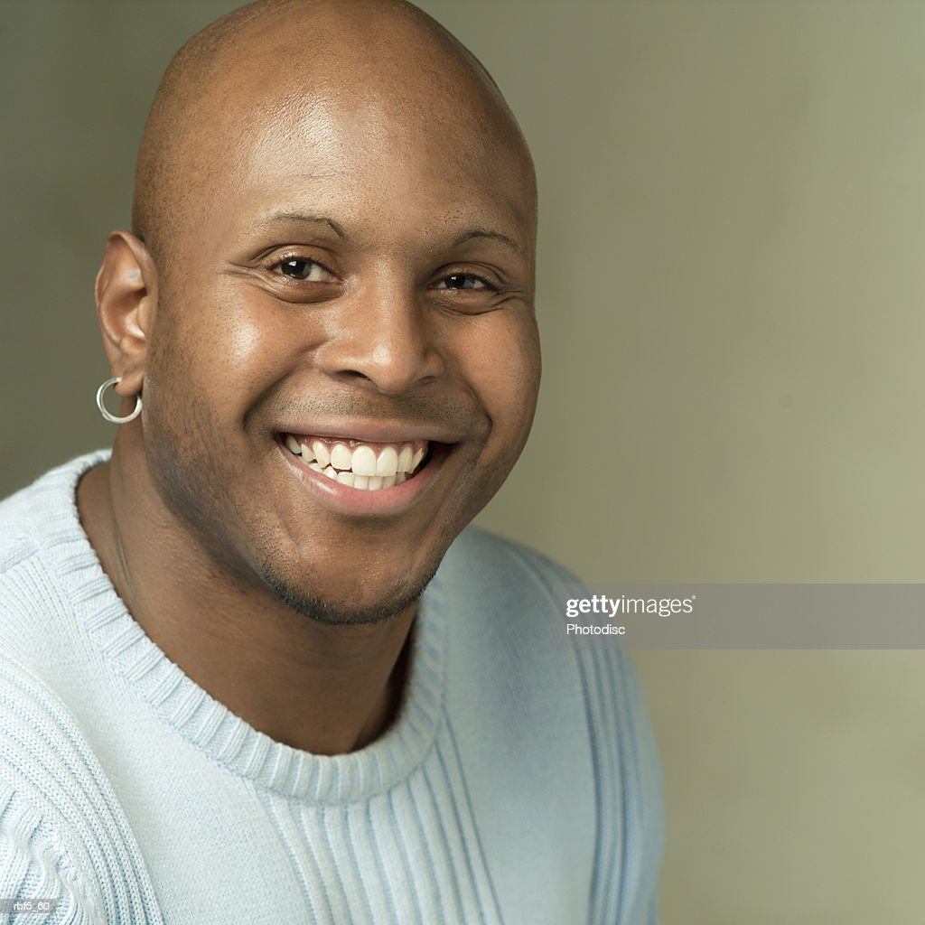 portrait of a african american man in a grey sweater as he smiles big into the camera : Stockfoto