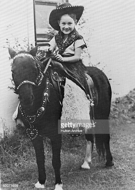 Portrait of a American rock and roll musician Buddy Holly at a very young age as he sits dressed as a cowboy on a pony probably in Lubbock Texas...