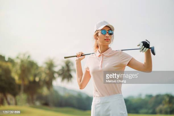 portrait of a asian chinese female golfer holding the golf club at the course - early retirement stock pictures, royalty-free photos & images