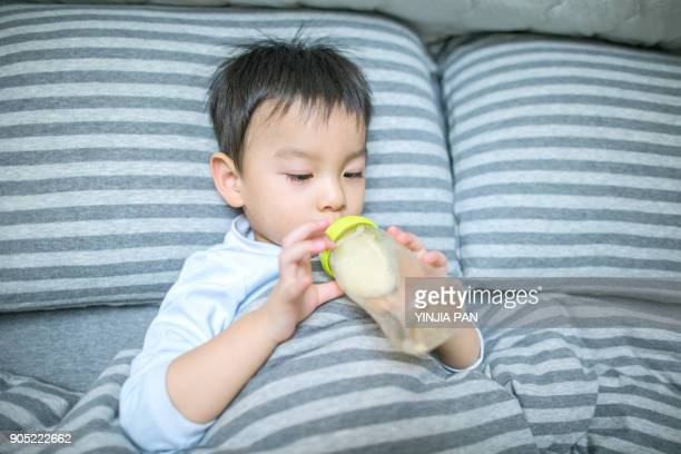 Portrait of a baby boy drinking from bottle on bed