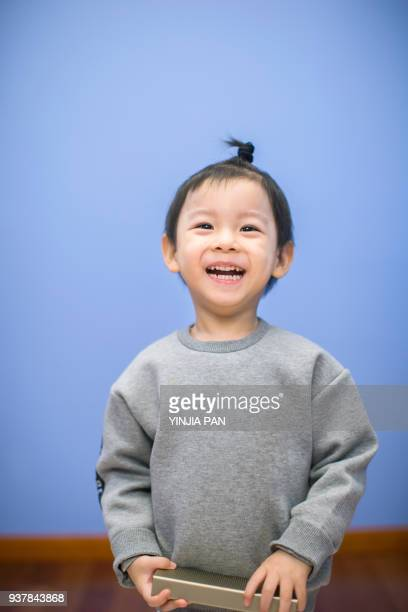 Portrait of a baby boy holding a speaker with smile at home