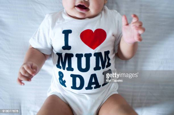 A portrait of a baby boy laying on his back with a print on his shirt saying i love mum and dad