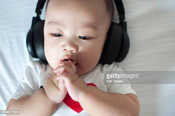 A portrait of a baby boy listening to a music using a headset