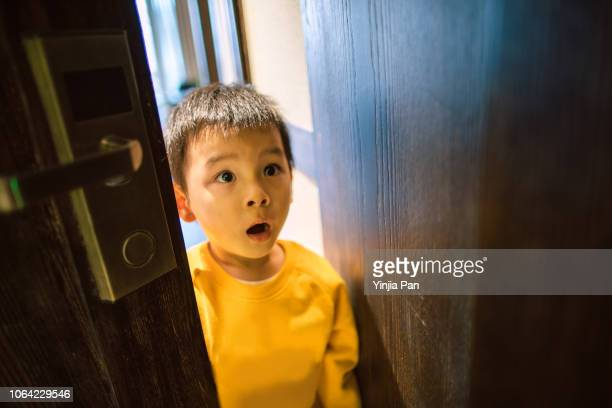 portrait of a baby boy opening door - innocence stock pictures, royalty-free photos & images