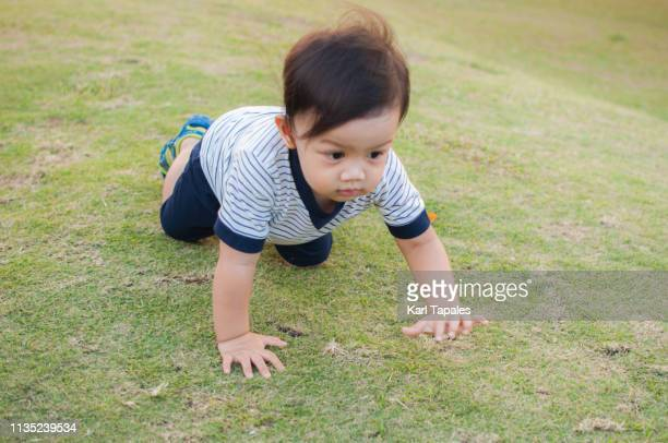 A portrait of a baby boy while playing outdoors