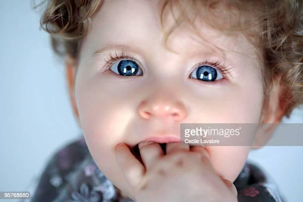 portrait of a baby girl biting fingers - chupando dedo - fotografias e filmes do acervo