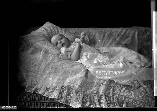 A portrait of a baby in a christening gown lying on a lace coverlet