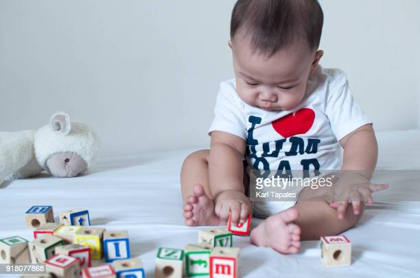 A portrait of a baby playing wooden alphabet toy cubes