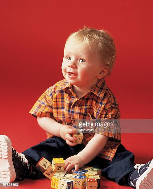 portrait of a baby (18-21 months) smiling playing with building blocks - one baby boy only stock pictures, royalty-free photos & images