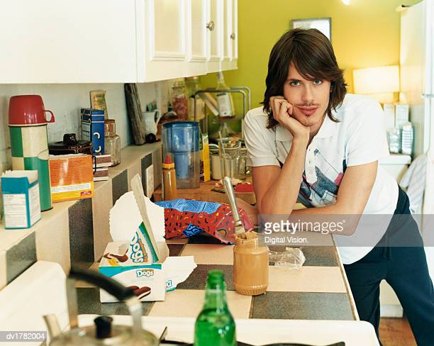 Portrait of a Bachelor Leaning Against a Counter in a Messy Kitchen
