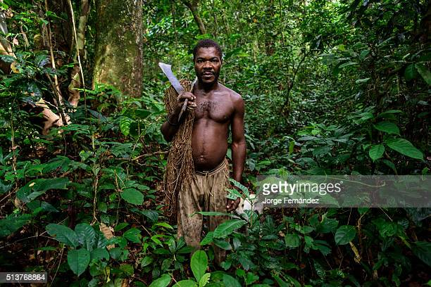 Portrait of a Bagdeli pigmy with a machete and net hunting with his dog in the jungle