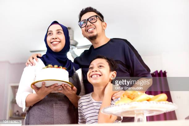 portrait of a baker family and a cake - malaysian culture stock pictures, royalty-free photos & images