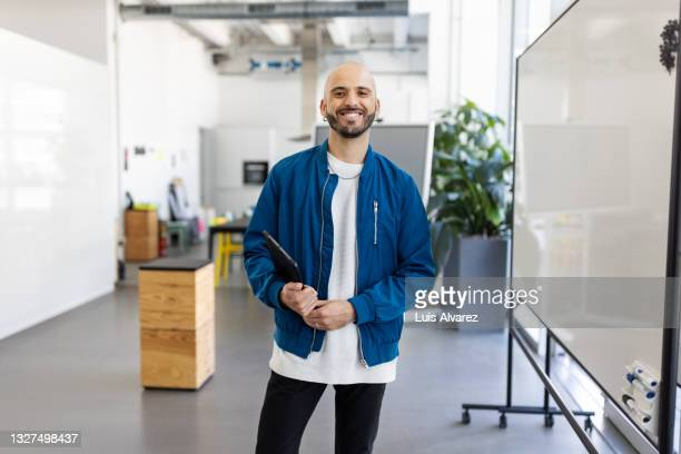 portrait of a bald businessman holding digital tablet - focus on foreground stock pictures, royalty-free photos & images