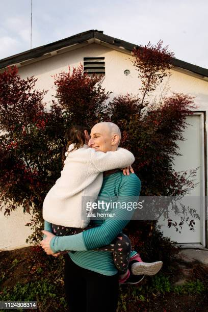 A portrait of a bald woman with her daughter