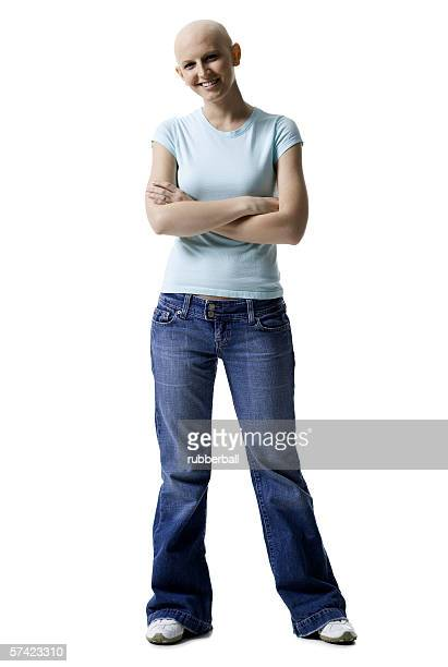 portrait of a bald young woman standing with her arms crossed - bald woman stock photos and pictures