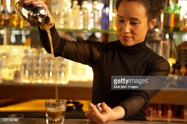 Portrait of a bartender pouring a drink at a bar