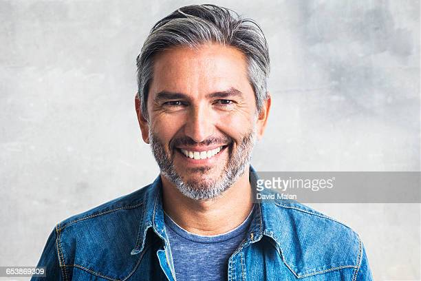 portrait of a bearded man in a denim shirt. - handsome 50 year old men stock photos and pictures