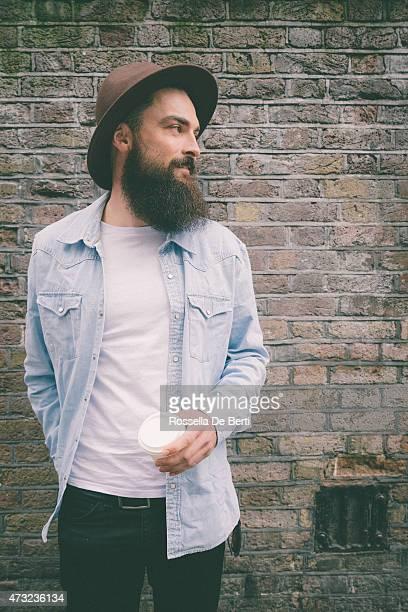 Portrait d'un homme barbu sur mur de briques arrière-plan