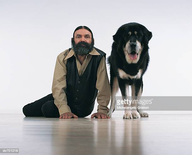 portrait of a bearded man sitting next to a tibetan mastiff - tibetan mastiff stock photos and pictures